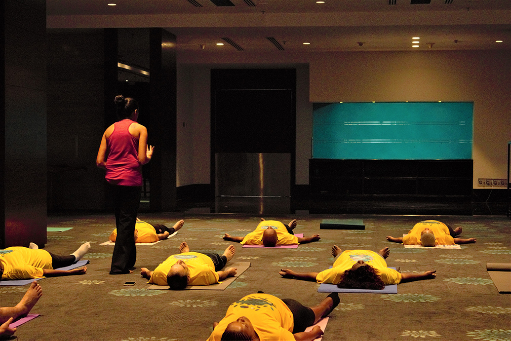 Employees do Shavasana Corpse Pose